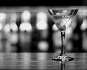 a cup of martini with olive on a old pub black and white conversion